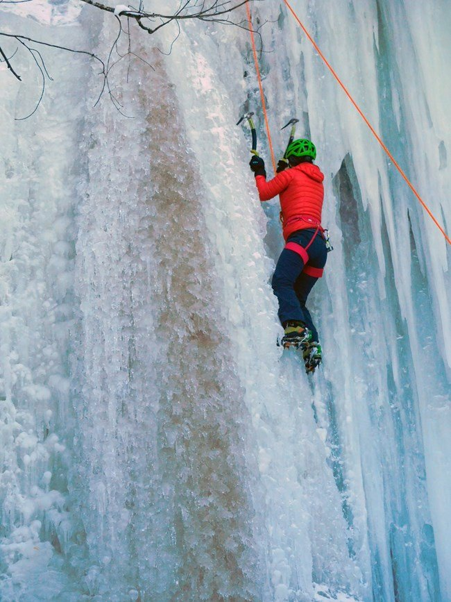 A woman climbs the ice curtains at Sant Point
